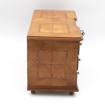 Side view : A Rare Miniature Fruitwood Inverted Break Center Chest Of Drawers With Checkered String Inlay. Unusual Central Locking Mechanism, German Circa 1780. Garden Court Antiques, San Francisco