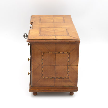 Side view: inlaid wood: A Rare Miniature Fruitwood Inverted Break Center Chest Of Drawers With Checkered String Inlay. Unusual Central Locking Mechanism, German Circa 1780. Garden Court Antiques, San Francisco